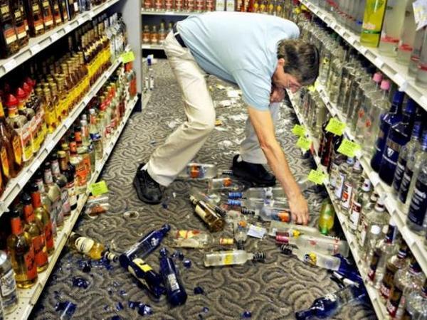 Мужчина наклонился за разбитой бутылкой