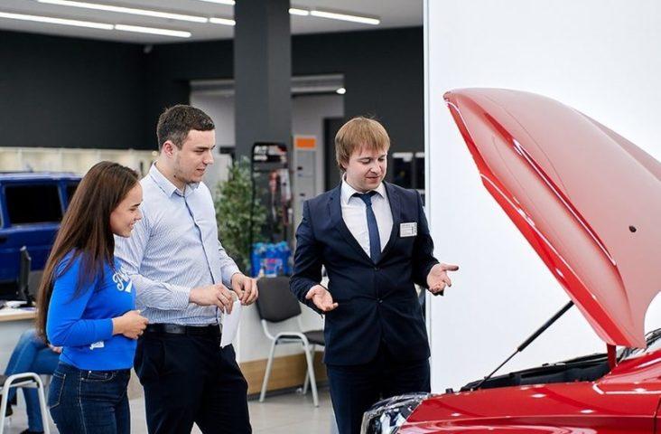 Менеджер показывает автомобиль паре