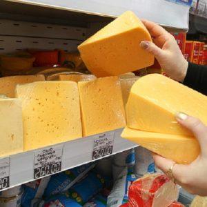 Женщина выбирает твердый сыр