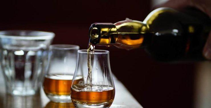 Виски наливают из бутылки в бокал