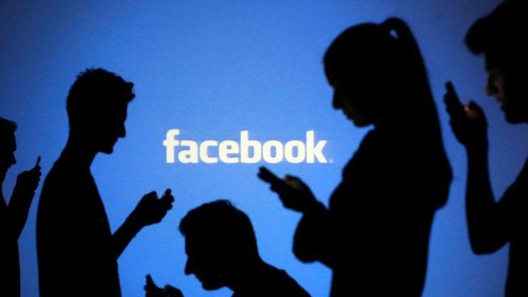 Тени людей на фоне надписи Facebook