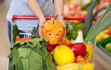 Девушка кладет копилку в корзину с продуктами