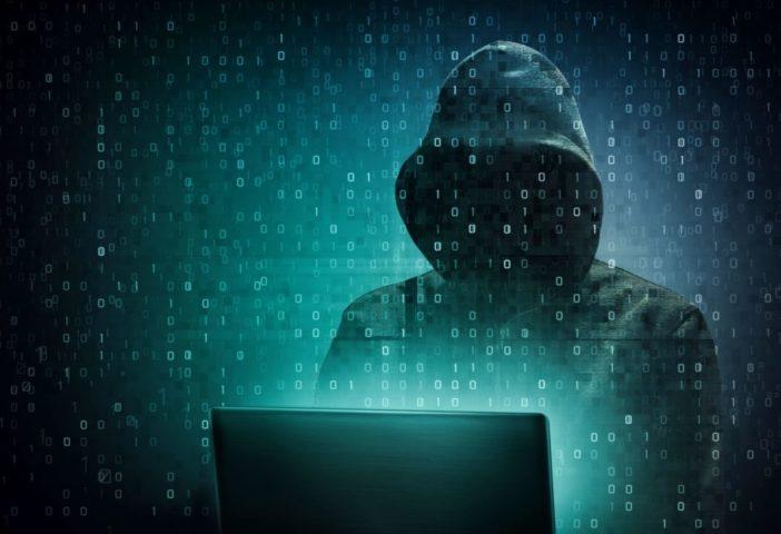 Человек в капюшоне за компьютером