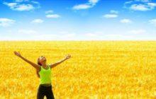 Счастливая девушка посреди поля пшеницы