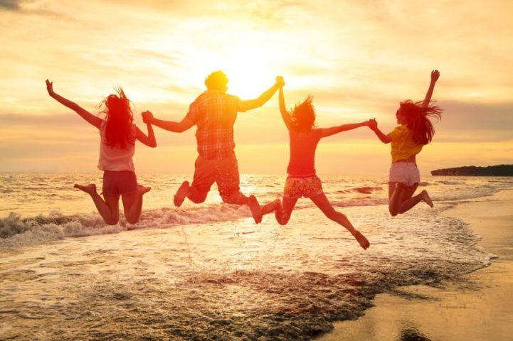 Люди прыгают на пляже