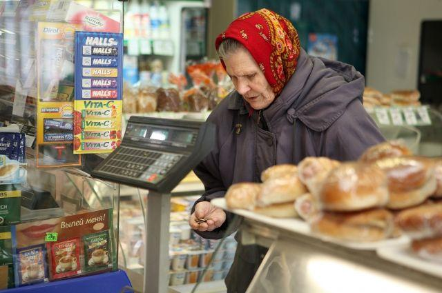 Пенсионерка покупает хлеб в магазине