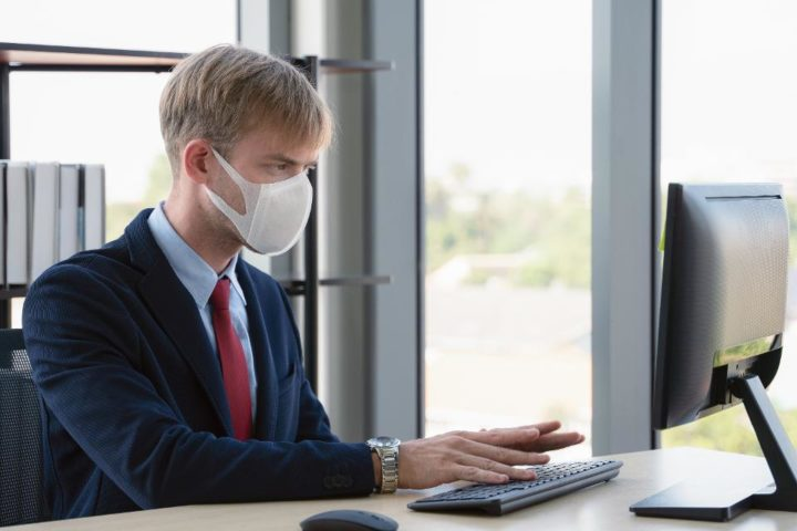 Мужчина в маске за компьютером