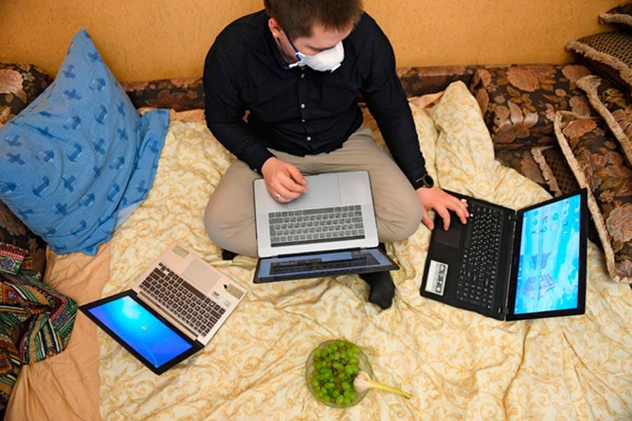 Мужчина с тремя ноутбуками