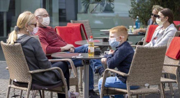 Семья за столиками в масках