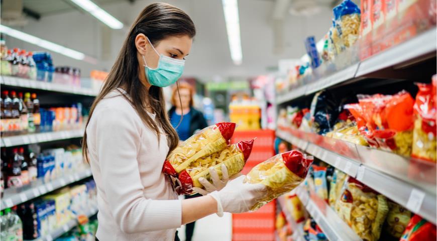 Девушка в маске выбирает макароны