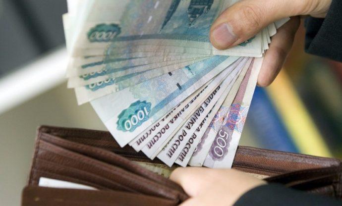 Человек кладет деньги в кошелек