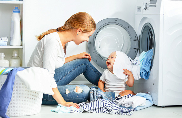 Женщина с малышом возле стиралки