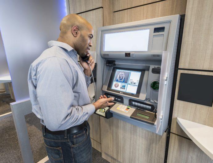 Мужчина общается по видеосвязи банкомата