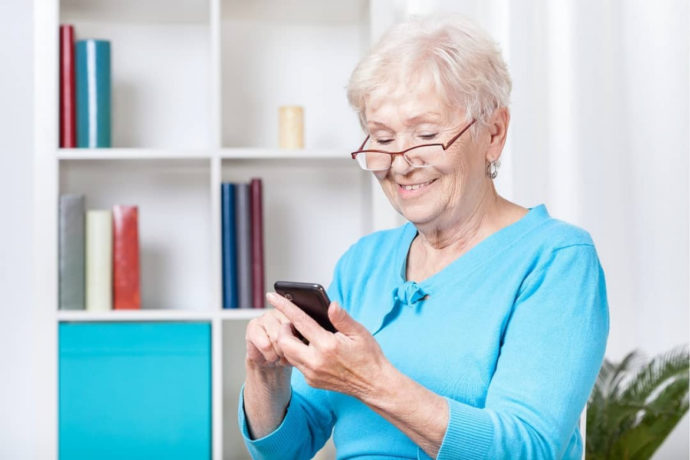 Пожилая женщина с телефоном в руках