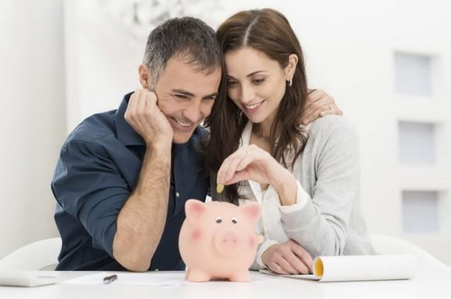 Мужчина и женщина складывают деньги в копилку