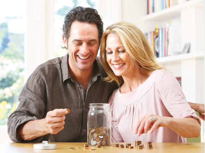 Мужчина и женщина складывают монеты в банку