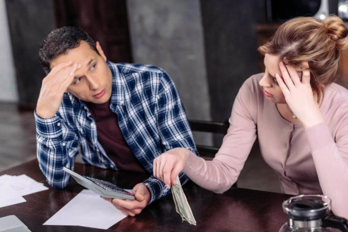 Молодая пара, деньги и калькулятор