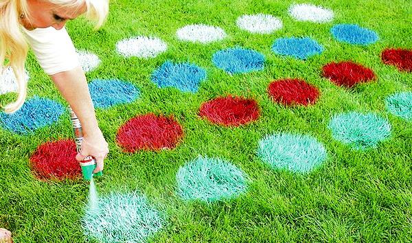 Девушка рисует твистер краской на траве