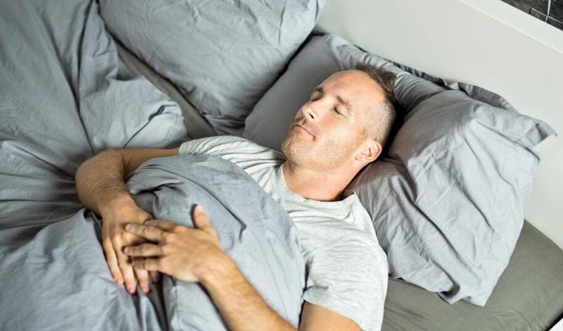 Спящий мужчина в кровати
