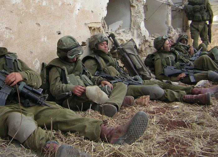 Солдаты спят возле развалин дома