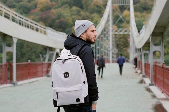 Мужчина с рюкзаком на мосту