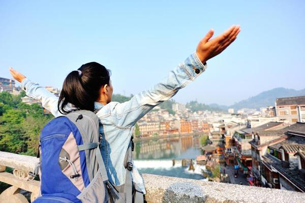 Девушка с рюкзаком на мосту