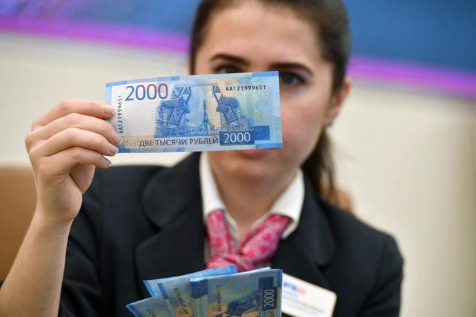 Девушка проверяет денежные купюры