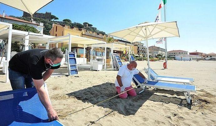 Мужчины измеряют расстояние между лежаками на пляже