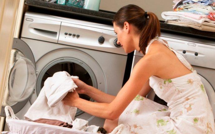 Девушка кладет вещи в стиральную машину