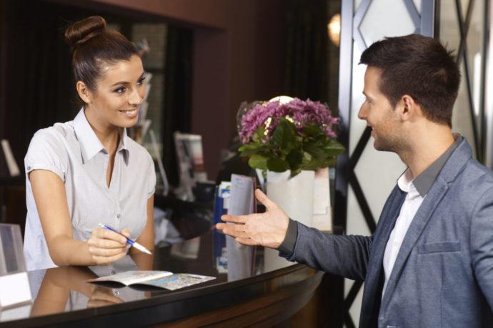 Девушка на ресепшене разговаривает с мужчиной