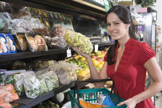 Девушка с упаковкой винограда в магазине