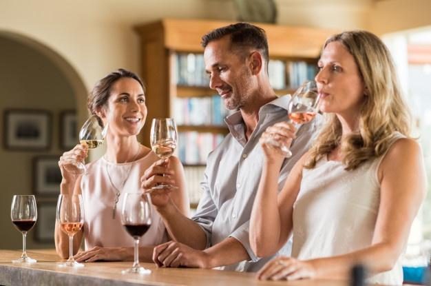 Две женщины и мужчина пьют вино