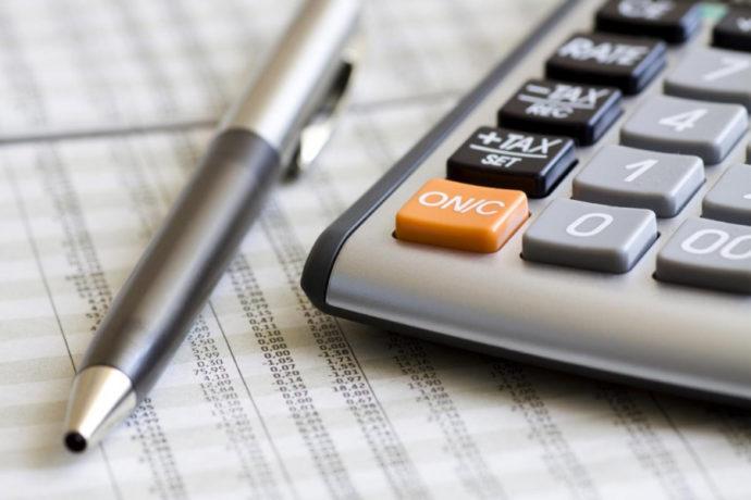 Калькулятор и ручка на столе