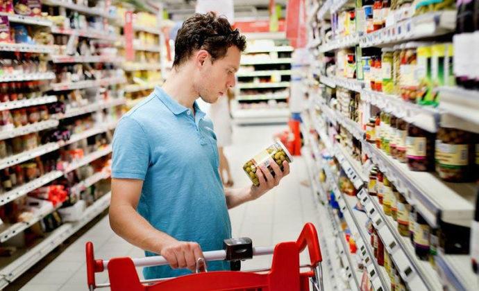 Мужчина в супермаркете выбирает оливки