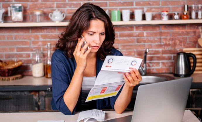 Женщина за столом с бумагой и телефоном
