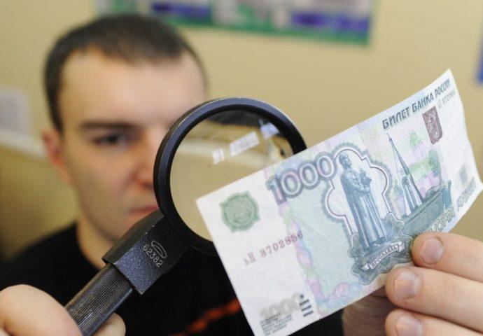 Мужчина смотрит в лупу на деньги