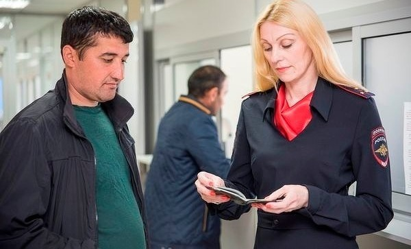 Сотрудник ФМС проверяет паспорт мужчины