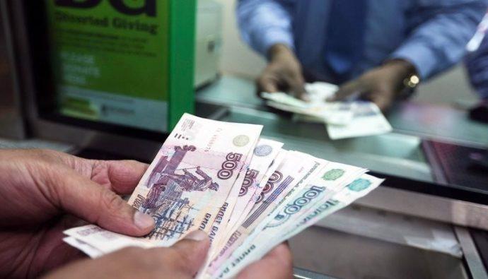 Деньги в руках у мужчины возле кассы