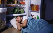 Мужчина спит у холодильника