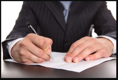 Мужчина в деловом костюме подписывает бумаги