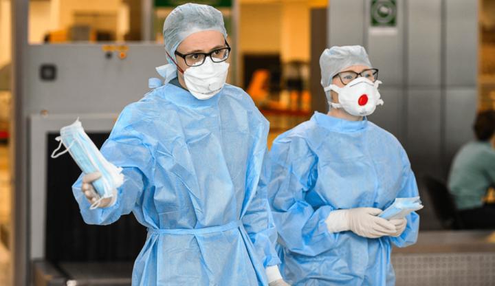 Медики в респираторах и защитных костюмах