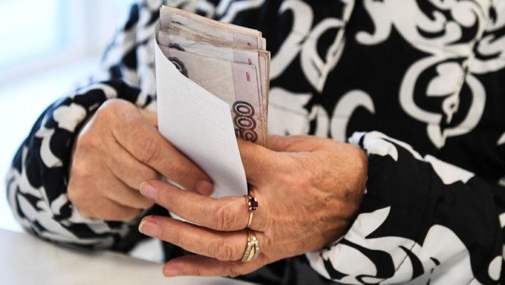 Пачка рублей в руках пожилой женщины