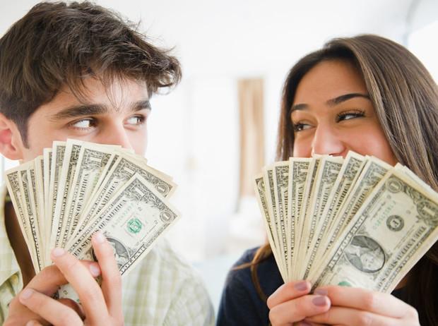 Парень и девушка прикрываются деньгами и улыбаются
