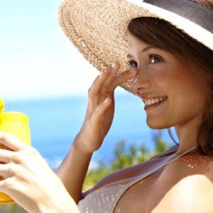 Девушка наносит солнцезащитный крем на лицо