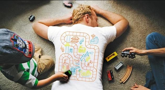 Мужчина лежит на полу, пока дети играют в машинки на его спине