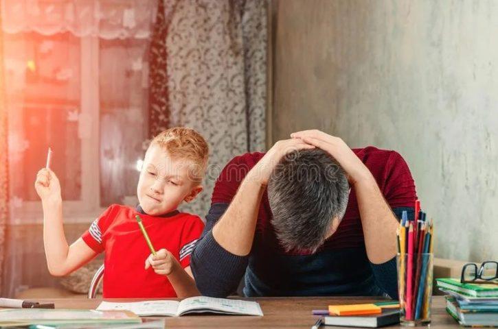 Папа держится за голову, пока ребенок играет с карандашами