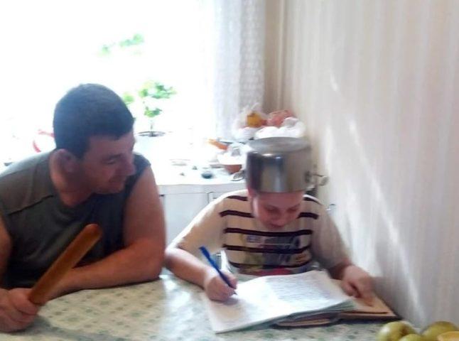Папа со скалкой и ребенок в кастрюле на голове делают уроки