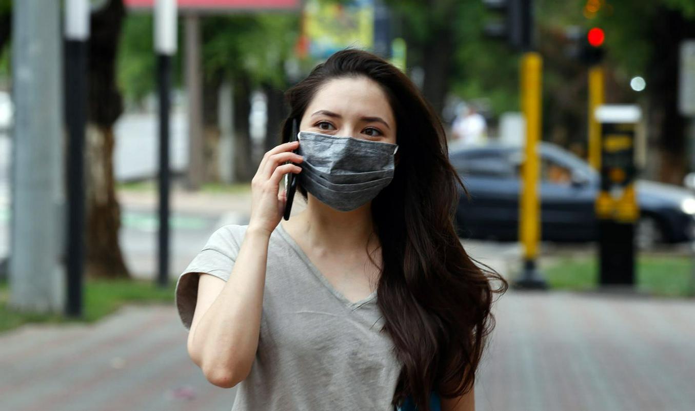 Девушка в маске говорит по телефону