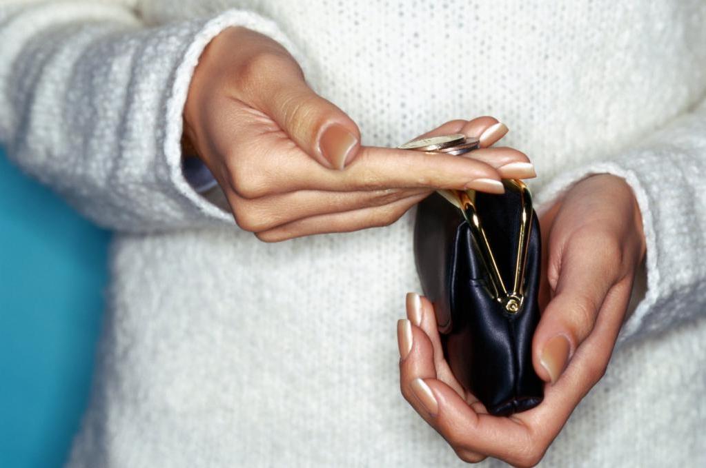Кошелек и монеты в женских руках