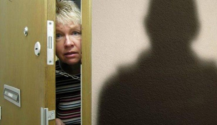 Женщина смотрит в приоткрытую дверь